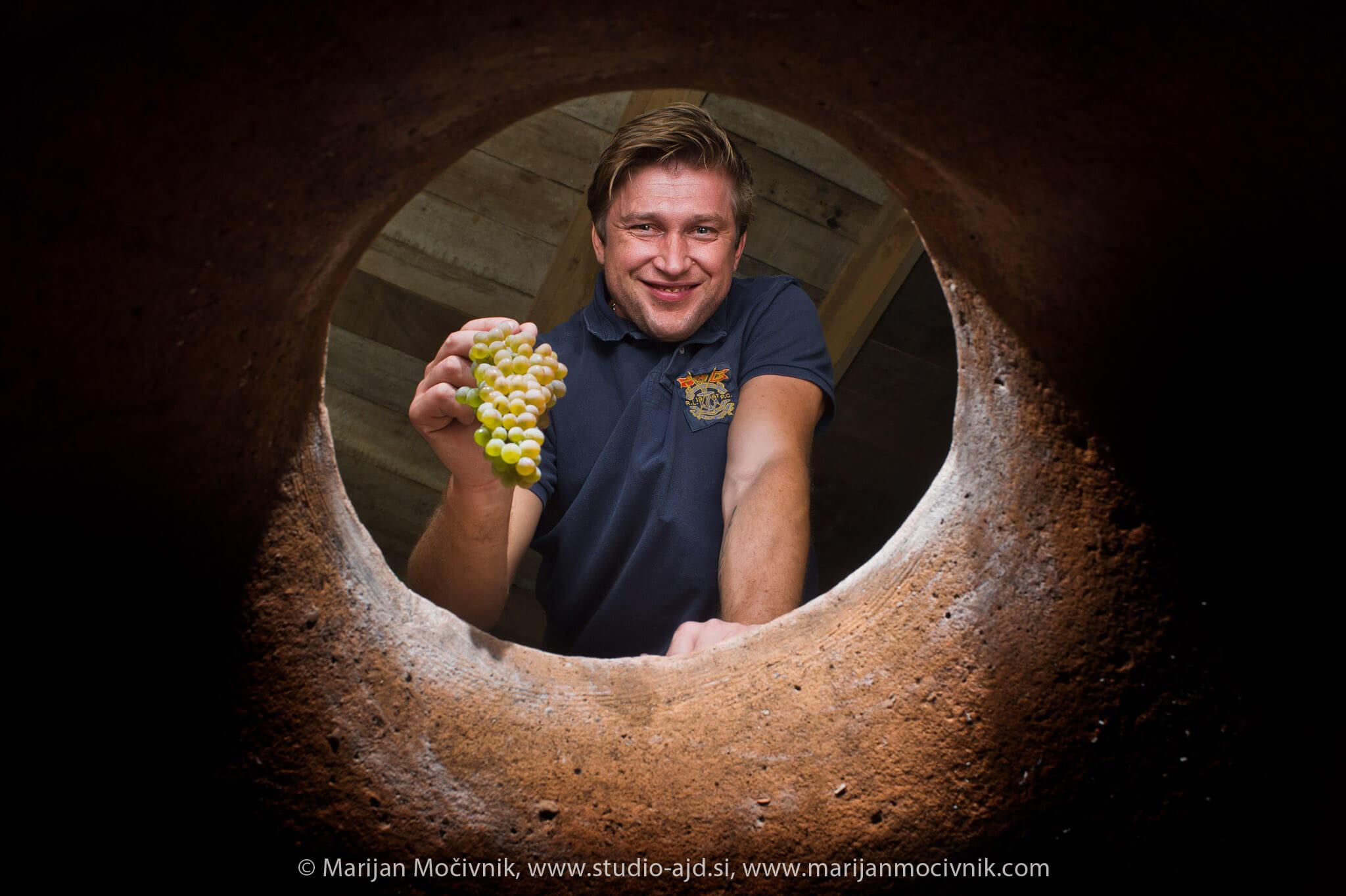 Vladimer Boisa z grozdom sorte Erkaciteli, pogled iz notranjosti več kot 100 let starega kvevrija (glinena posoda za vino, vkopana v tla) v njegovi kleti v Gruziji.